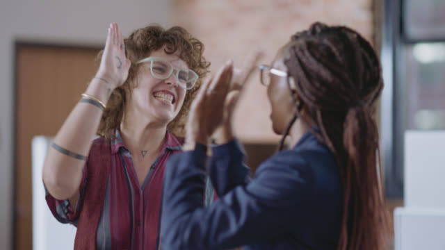 lively businesswomen celebrate together with high-fives and clapping - colleague stock videos & royalty-free footage