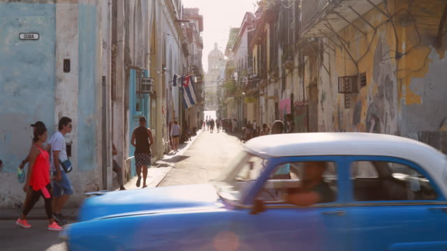 stockvideo's en b-roll-footage met lively crossroad in central havana with vintage cars - cuba