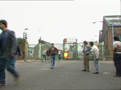 ; b) england: liverpool: ext schoolboys in uniform l-r to arrive at locked gates of comprehensive school tms children outside gates pull out across... - school bell stock videos & royalty-free footage