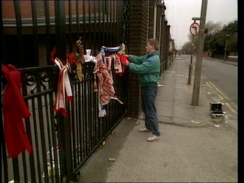 Liverpool ENGLAND Liverpool Anfield NIGHT Fans putting flowers at gates of Liverpool club some weep and hug Ext Shankly gates with tributs on them...