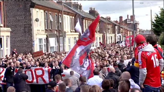 Liverpool fans protest against US owners Large crowd of supporters along street towards stadium carrying banner and chanting for Hicks and Gillet to...