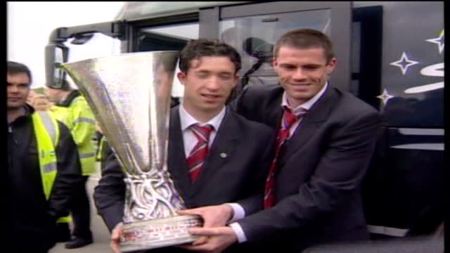 Liverpool FC agree takeover bid by American businessmen TX Robbie Fowler and Jamie Carragher holding UEFA cup trophy