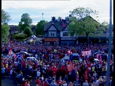 Liverpool FC return after Champions League victory airport arrival/ parade LMS Fans sitting on roof of shops on parade route TILT DOWN fans gathered...