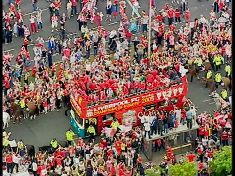 Liverpool FC return after Champions League victory airport arrival/ parade AIR VIEW Bus along tree lined route AIR VIEWs Bus along past large crowds...