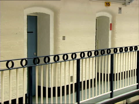 liverpool liverpool prison woman prison officer walking away along landing in cell block / cell doors / man leaning on railings tilt down cell doors... - prison cell door stock videos & royalty-free footage
