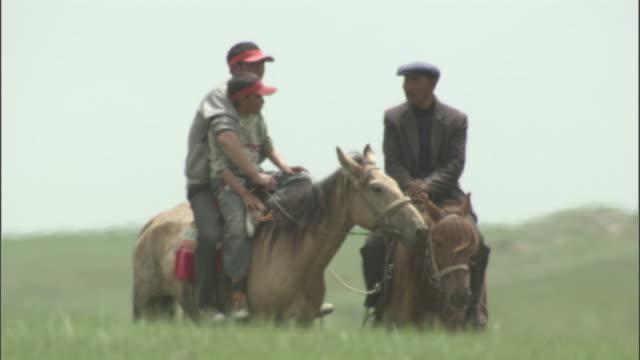 Livestock herders on horseback in heat haze, Bayanbulak grasslands.