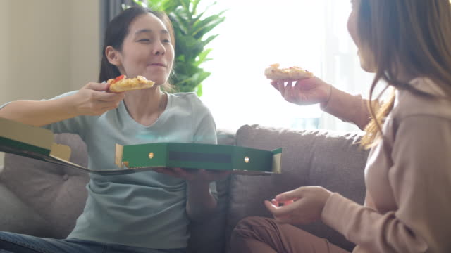 living lifestyles having pizza and chatting at home - genderblend stock videos & royalty-free footage