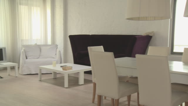 ws living room area of loft decorated entirely in white/ pan ms white dining table surrounded by chairs/ pan living room area/ berlin, germany - speisezimmer stock-videos und b-roll-filmmaterial