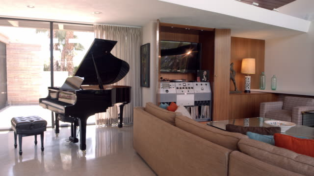 WS TS living room with grand piano and L-shaped sofa around glass coffee table
