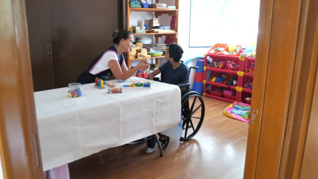 living with terminal disability - latino boy with celebral palsy in day care - disability stock videos & royalty-free footage
