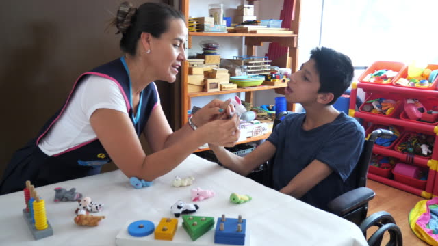 living with terminal disability - latino boy with celebral palsy in day care - co ordination stock videos & royalty-free footage