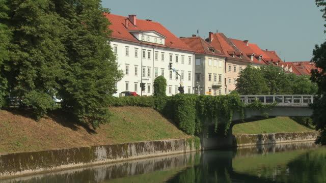 ws td ljubjanica river with bridge, man reading on riverbank, ljubljana, slovenia - korslagda ben bildbanksvideor och videomaterial från bakom kulisserna