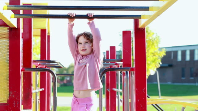 MS Llittle girl playing on  monkey bars at playground / Toronto, Ontario, Canada