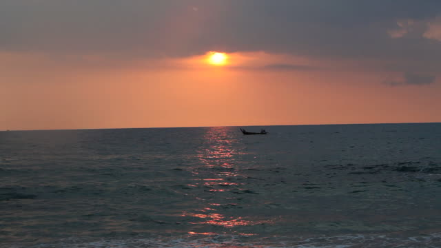 WS Llongtail boat passing through sea water at sunset / Koh Lanta, Krabi,Thailand