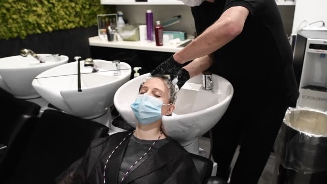 llongueras stylist juan manuel guijarro washes the head of a client at the llongueras hairdressing salon during the first day of reopening to the... - beauty salon stock videos & royalty-free footage