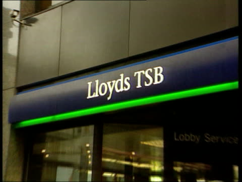 Lloyds TSB launches bid for Abbey National LIB London Branch of Lloyds TSB bank ZOOM IN sign SIDE MS Men using cash dispensers TILT UP sign GV...