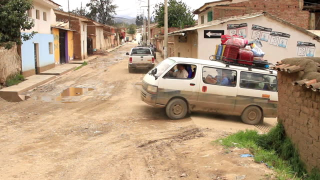 A loaded, dirty van travels through a Peruvian village.