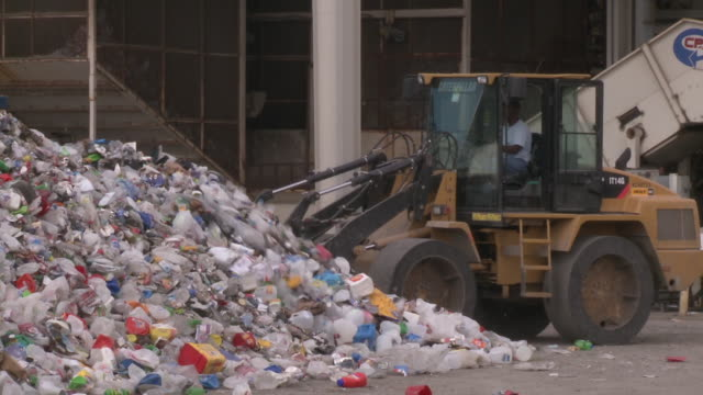 WS ZI PAN Loader piling mound of mixed recyclables at municipal solid waste facility / Austin, Texas