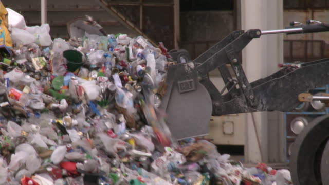 cu pan loader piling mound of mixed recyclables at municipal solid waste facility / austin, texas - 環境問題点の映像素材/bロール