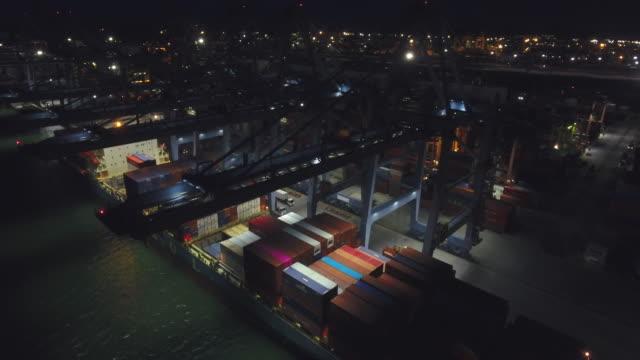caricamento di container cargo in nave in porto industriale di notte, colpo ravvicinato - porto marittimo video stock e b–roll