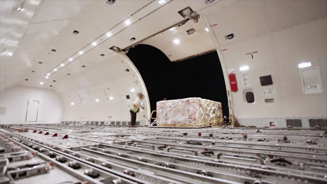 loading cargo inside airplane cargo hold - cargo container stock videos & royalty-free footage