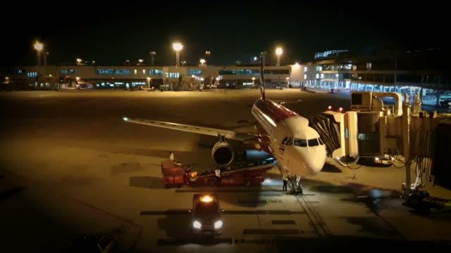 vidéos et rushes de chargement de l'exploitation de fret pour l'avion commercial la nuit - piste d'envol