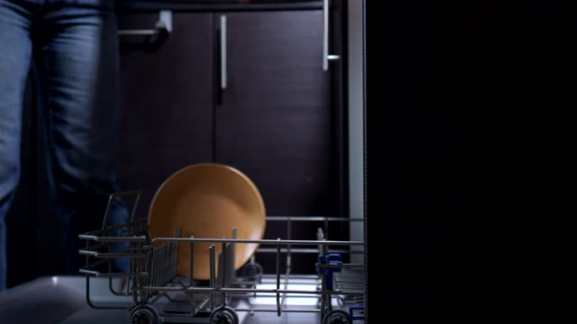 loading dishes to a dishwasher - lavastoviglie video stock e b–roll