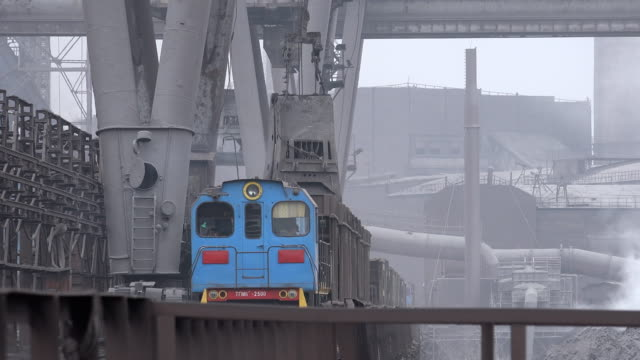 loading of iron ore at metallurgical factory yard - schwer stock-videos und b-roll-filmmaterial