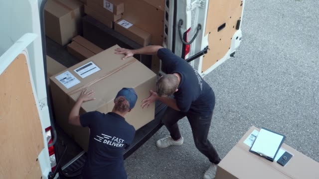 loading packages in a delivery van - carrying stock videos & royalty-free footage