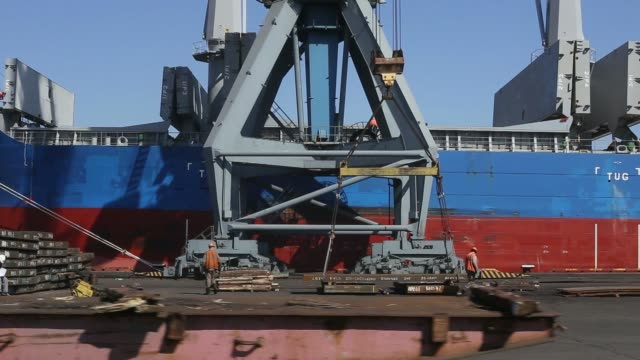 a loading vehicle drives past the loch lomond cargo vessel during the loading of steel for export at the port of mariupol one of ukraines biggest... - minerale di ferro video stock e b–roll