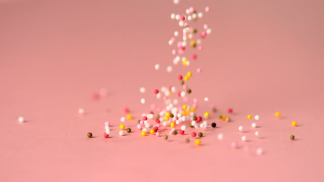 Loads of sprinkles falling on pink surface
