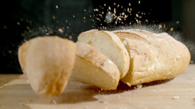 slo mo td loaf of bread falling on a table - bread stock videos & royalty-free footage