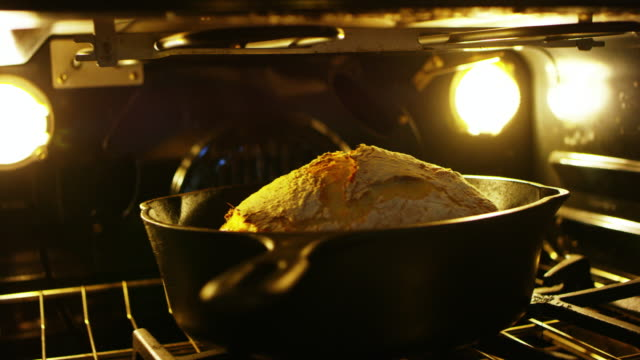 a loaf of sourdough bread bakes inside of the oven in a cast iron skillet - pane a lievito naturale video stock e b–roll