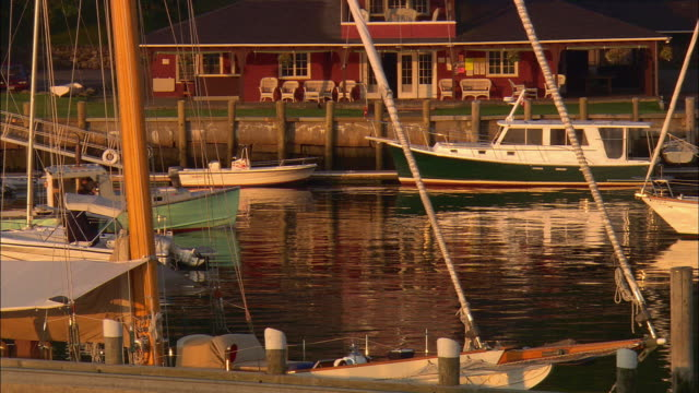 vidéos et rushes de ms, lobster boat passing by sailboats moored in harbor at sunset, camden, maine, usa - maine