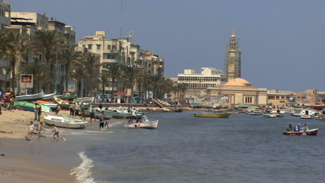 vidéos et rushes de ws local beach with fishermen's boats and children playing, alexandria, egypt - alexandrie