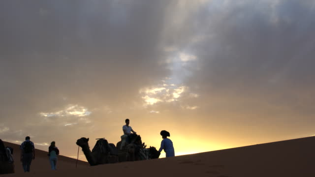 Local Bedouins leading a small caravan of camels with tourist into the dunes of Erg Chebbi, Saharan Morocco