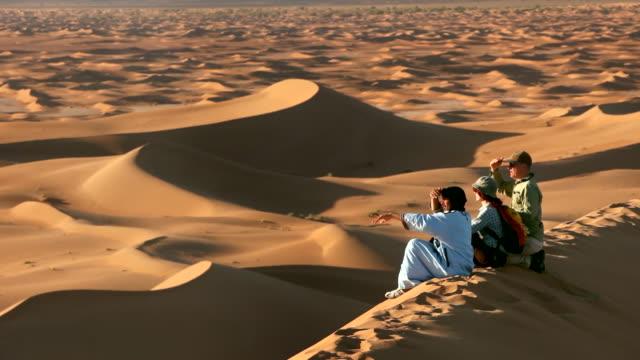 Local Berber man and tourists on Sand-Dune, Erg-Chigaga sand dunes. Sahara Desert, Mhamid, Morocco