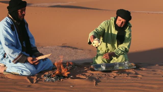vidéos et rushes de local berber nomads make tea, erg-chigaga sand dunes. sahara desert, mhamid, morocco - maroc