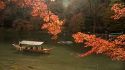 local boat in Katsura river amid autumn Leaf forest at Arashiyama