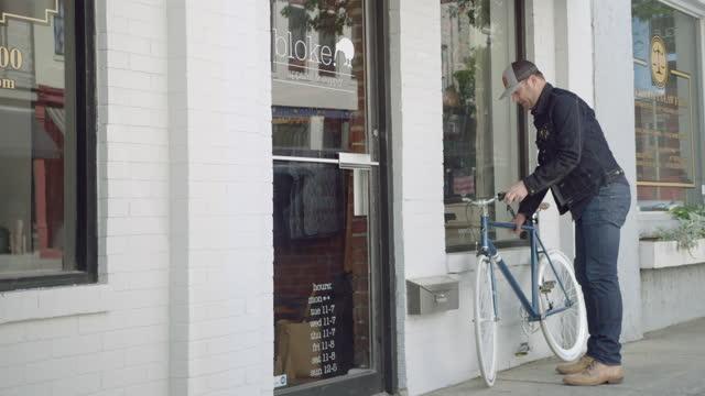 vídeos y material grabado en eventos de stock de local business owner rides bicycle up to downtown storefront and unlocks shop. - llegada