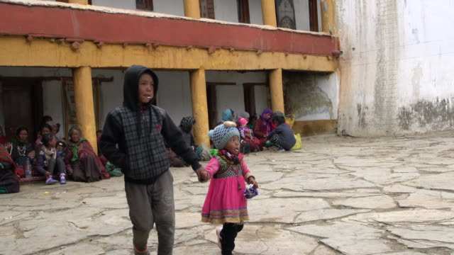 local chang-pa children and women gathering in the inner yard of the korzok tibetan buddhist monastery expecting the beginning of the buddhist temple service, korzok monastery, ladakh, india - preschool child stock videos & royalty-free footage