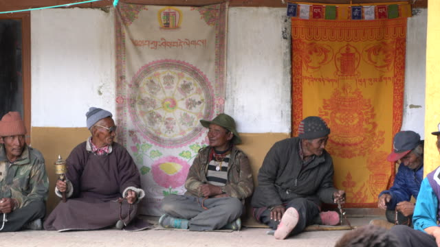 local chang-pa herdsmen sitting in the inner yard of the korzok tibetan buddhist monastery expecting the beginning of the buddhist temple service, korzok monastery, ladakh, india - other stock videos & royalty-free footage