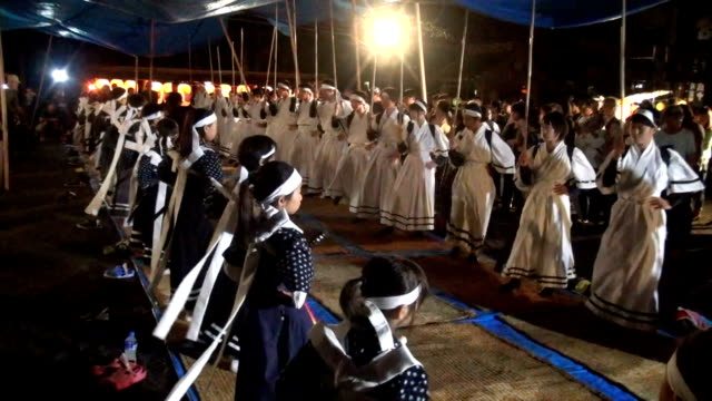 Local children dressed in traditional costumes danced with swords and fans in their hands as elders in white shirts and neckties beat on drums at the...