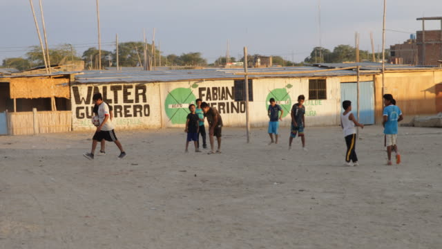 Local children playing football in a desert slum in Piura Chile The goal is made of bamboo branches Painted on the walls are the names Walter...
