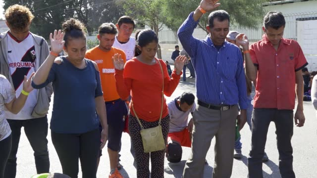 vídeos de stock, filmes e b-roll de a local christian church 'the taf church of tijuana' distributed food and prayed with members of the central american migrant caravan that are... - política e governo