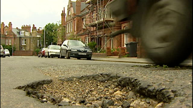 local councils lack money for road repairs; ext car avoiding pot hole in road various shots traffic along road in need of repair tracking shot... - foro video stock e b–roll