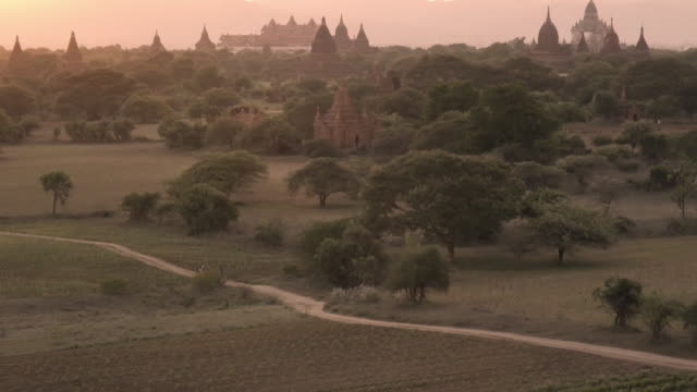w/s local cyclists and temples of bagan at sunset, myanmar - myanmar stock-videos und b-roll-filmmaterial