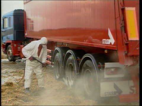 local elections postponed because of foot and mouth disease cumbria great orton man spraying wheels of lorry with disinfectant pull gv lorry trailor... - mass grave stock videos and b-roll footage