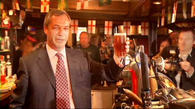 results england essex benfleet photography** nigel farage mep raising pint glass of beer as standing behind bar of pub farage posing for photocall as... - pint glass stock videos & royalty-free footage