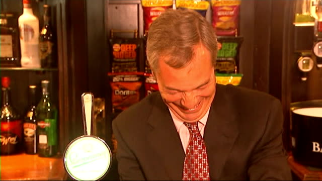 nigel farage visits pub in benfleet; int **beware flash photography** farage in pub chatting as drinking pint / farage pulling pint for photocall /... - pint glass stock videos & royalty-free footage
